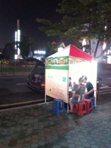 """A couple with a young baby visiting a fortuneteller in his  """"tent"""" near Ilsan beach. He's reading out of a set of black books. That's his van with the hatch open behind the stand."""